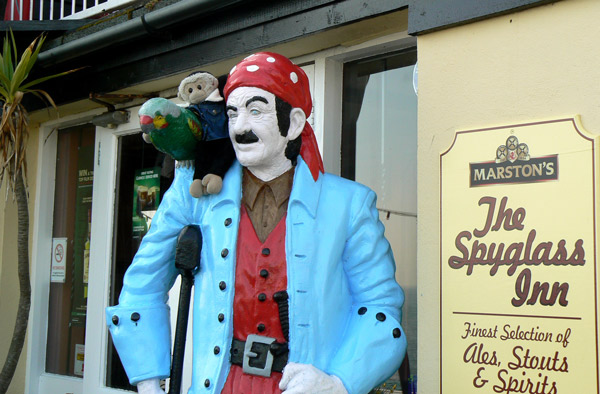 Mooch monkey sits with the parrot on the shoulder of the pirate outside the Spyglass Inn, Ventnor, Isle of Wight.